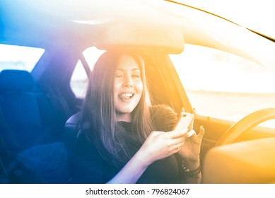 Portrait of beautiful asian brunette woman holding in hands cell mobile phone inside new car through transparent window background.Copy space for inscription. funny comical young girl show tongue