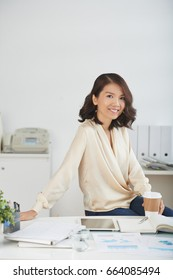 Portrait of beautiful Asian businesswoman posing at office desk with paper coffee cup in her hand