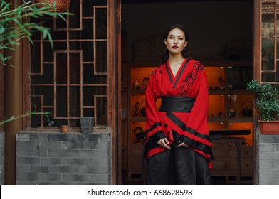 Portrait of beautiful asian chinese brunette woman wearing red national clothes. She has purple lipstick make up. She is standing in front of tea house entrance with chinese interior.