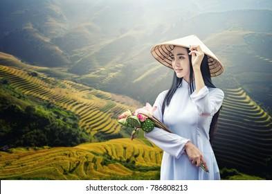 Portrait of Beautiful Asian girls with Ao Dai on Green Rice fields on terraced in Muchangchai, Vietnam Rice fields prepare the harvest at Northwest Vietnam.Vietnam landscapes.