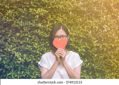 Portrait of beautiful Asian glasses girl holding red heart with sunlight on plants background. Valentines day, copy space, soft focus.