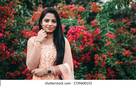 Portrait of a beautiful Asian/ Indian young woman wearing Indian dress. Soft warm vintage color tone , Flowers in background.
