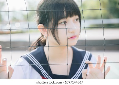 Portrait of beautiful Asian japanese high school girl uniform looking with net in green background