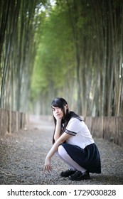 Portrait of beautiful Asian japanese high school girl uniform looking with bamboo forest background