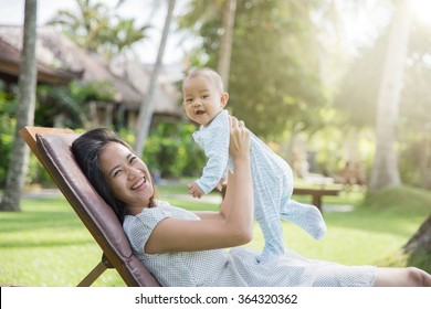 portrait of a beautiful asian mother having fun with his baby on a sunny day