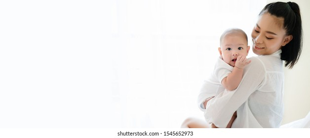 Portrait of beautiful Asian mother hugging his newborn son in the bedroom. Baby is adorable. Mom is smiling happily with the child healthy. Nursery for young children. Banner with copy space