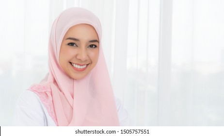 Portrait beautiful asian muslim woman model posing with pink headdress on white curtain background in close-up view.