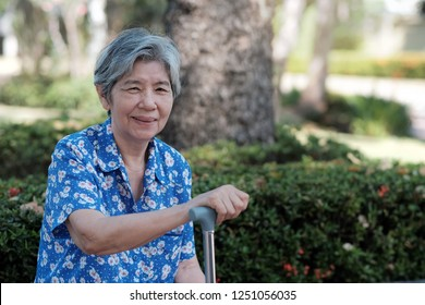 Portrait Beautiful Asian old women smiling and looking at camera. She holding crutch and sitting in park. Concept Elder Day, love and take care of elderly. Good health and happy old people.
