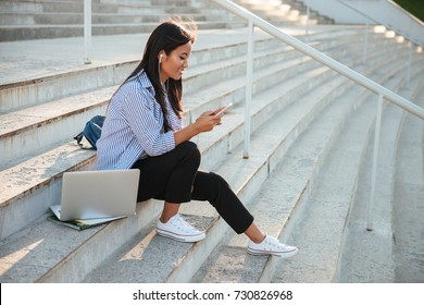 Portrait of beautiful asian student, listening to music, holding mobile phone, sitting on the city stairs