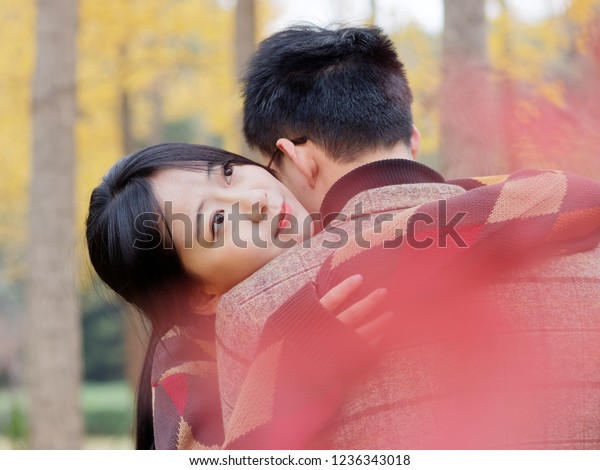 Portrait of beautiful Asian wife embracing husband. Close up Chinese woman looking at camera, man rear view Attractive affectionate couple in love, romantic relationship just a married engaged concept