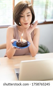 Portrait of beautiful Asian woman celebrates her birthday through video call virtual party with friends in quarantine time. Authentic decorated home workplace. Coronavirus outbreak 2020