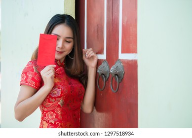 Portrait of beautiful asian woman in Cheongsam dress,Thailand people,Happy Chinese new year concept,Holding red envelope red.