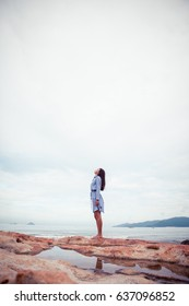 A portrait of beautiful asian woman in dress stand on a stone by the sea and looks up