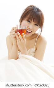 a portrait of beautiful asian woman drinking a hot tea on the bed