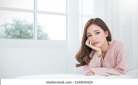 Portrait of beautiful asian woman feeling depress stress in bedroom. Sad face asian girl sit near window in winter. Beauty treatment perfect clear skin japanese korean makeup  lifestyle concept banner
