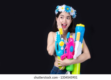 Portrait Beautiful asian woman holding Plastic gun on black background.