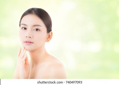 Portrait of beautiful asian woman makeup of cosmetic, girl hand touch cheek and smile attractive, face of beauty perfect with wellness on nature green background with skin healthcare concept.