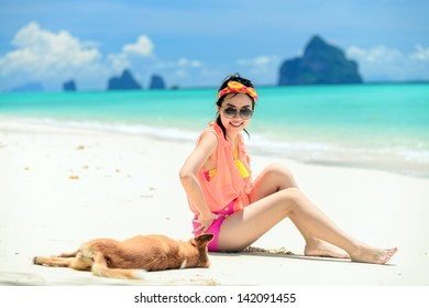 A portrait of beautiful asian woman on relaxing the beach with dog