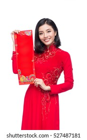 Portrait of a beautiful Asian woman on traditional festival costume Ao Dai showing  New Year scrolls Tet holiday. Lunar New Year.