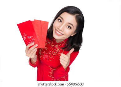 Portrait of a beautiful Asian woman on traditional festival costume Ao Dai holding red pocket - lucky money. Tet holiday. Lunar New Year.