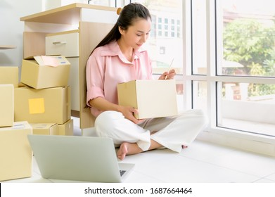 Portrait of beautiful Asian woman packing a parcel boxes close up. E-Commerce and online shopping concept.