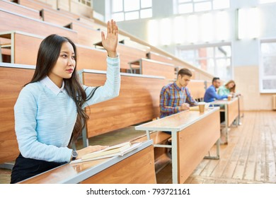 Portrait of beautiful Asian woman raising hand during class at college, copy space with people in background