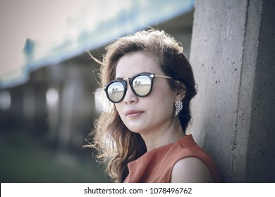 Portrait of beautiful Asian woman in red dress and wearing sunglasses with reflection of house view. Taken with low depth of field technic. Process in old style vintage.
