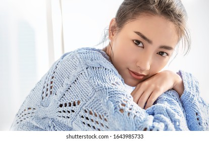 Portrait of beautiful asian woman relax face in winter bedroom. Closeup sexy beauty fashion girl healthy makeup facial treatment perfect glow skin. Smile happy hygge asia korean girl in blue sweater