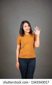 Portrait of beautiful Asian woman standing in casual clothing and greeting you waving her arm