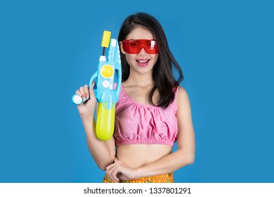 Portrait Beautiful asian woman Take Plastic gun on blue background.  water gun party or Songkran festival, Thailand. Thai New Year's Day