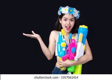 Portrait Beautiful asian woman Take Plastic gun on black background.  water gun party or Songkran festival, Thailand. Thai New Year's Day