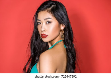 9e327be97a Portrait of a beautiful asian woman in turquoise swimsuit standing half-turned  and looking at