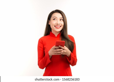 Portrait of beautiful Asian woman using mobile phone and wearing red Ao dai on white background.