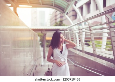 Portrait beautiful asian woman walking and holding mobilephone in the city,Happy and smiling