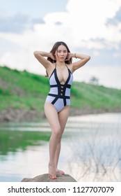 Portrait of beautiful asian woman wear bikini on the rock side sea in the evening,Lifestyle of modern women,Thailand people