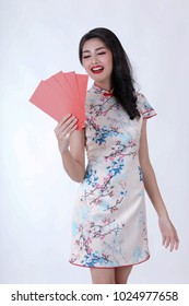 Portrait of beautiful asian woman in white chinese dress traditional cheongsam. chinese new year concept.Smiling Chinese woman is holding red packet of Ang Pao and gold present of Chinese New Year.