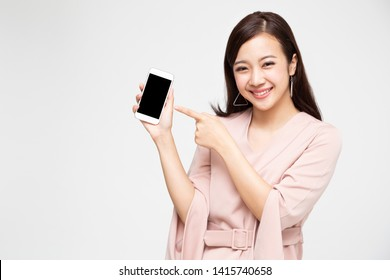 Portrait of beautiful Asian wowan showing or presenting mobile phone application on hand isolated over white background