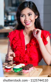 Portrait of a beautiful Asian young woman smiling while buying delicious cupcakes in a trendy sweetshop with various confections