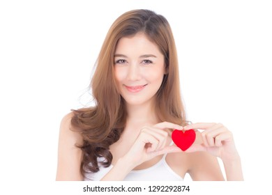 Portrait of beautiful asian young woman holding red heart shape pillow and smile isolated on white background, valentines day, holiday concept.