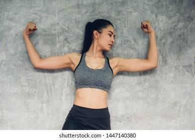 Portrait of beautiful asian young woman wearing  sportswear posing in gym