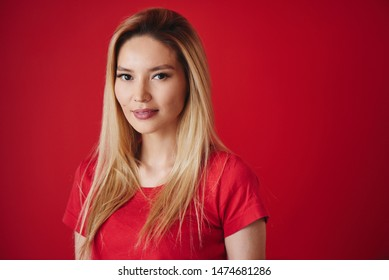 Portrait of beautiful asian young woman in t-shirt. Attractive kazakh blonde girl smiling on red background in studio isolated