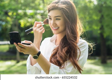 Portrait of beautiful asian young woman make up to her face in the park, Beauty and fashion concept.