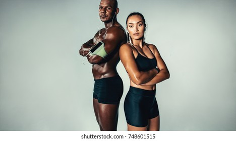 Portrait of beautiful athletic couple standing together on grey background. Muscular young man and woman with arms crossed looking at camera.
