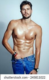 Portrait of a beautiful athletic men in jeans, studio photo