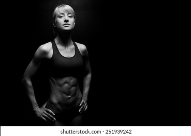 Portrait of a beautiful athletic woman on dark background