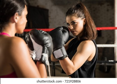Portrait of a beautiful and athletic young woman standing in front of her opponent looking ready to fight in a boxing ring