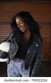 Portrait of beautiful and attractive african american woman in black lather motorcycle jacket, holds fullface retro helmet, sways her hair and head in movement, smiles and laughs