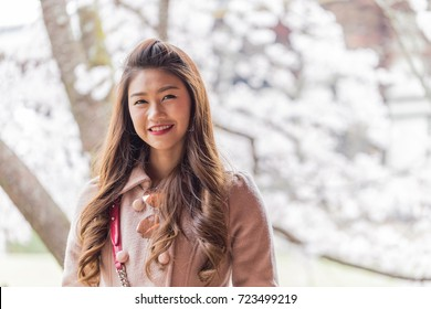 Portrait Beautiful Attractive Asian woman smile with cherry blossom or sakura flower feeling so happiness and cheerful