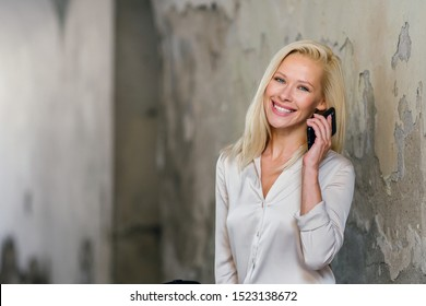 Portrait of a beautiful, attractive, elegant and sexy Caucasian platinum blond woman in a cream blouse and white pants smiling as she talks happily on her smartphone device on a street in the day.