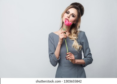 Portrait of beautiful attractive fashion model in grey dress with makeup and hairstyle, standing, holding red tulip and looking at camera with passion. indoor studio shot, isolated on grey background.